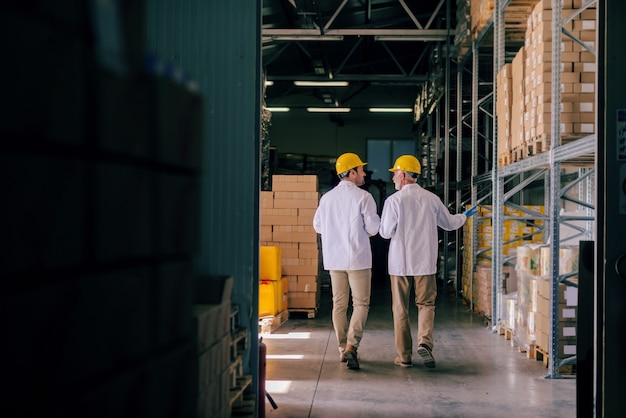 Двое складских рабочих в униформе и шлемах на головах идут по складу и разговаривают. спиной повернулся.