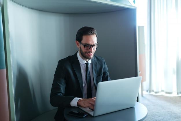 ラップトップを使用して彼のオフィスに座っているフォーマルな服装の成功したマネージャーの笑顔。