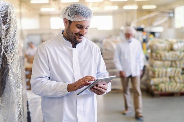 Крупным планом смотритель в униформе с помощью планшета для проверки данных, стоя на пищевой фабрике.
