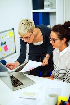 深刻なプロの自信を持って起業家の短い髪の毛がオフィスで新しい同僚と書類やラップトップを持ちながら働いています。