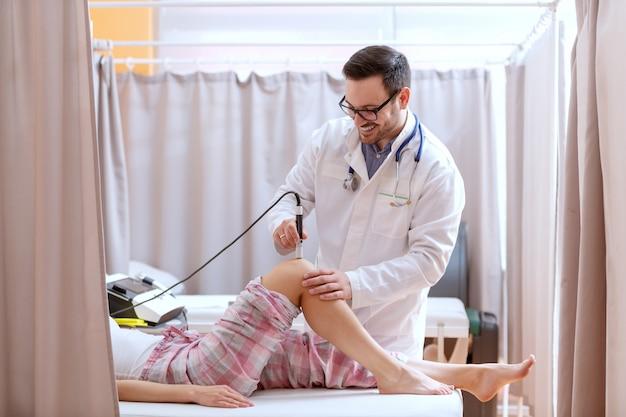 鎮痛のための電気分解装置を扱う整形外科医。患者は病院のベッドに横たわっています。