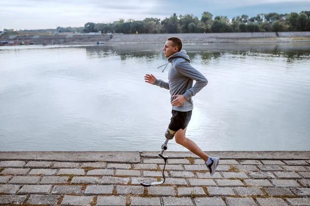 スポーツウェアと岸壁で実行されている義足で健康な白人の障害を持つスポーツマンの側面図です。