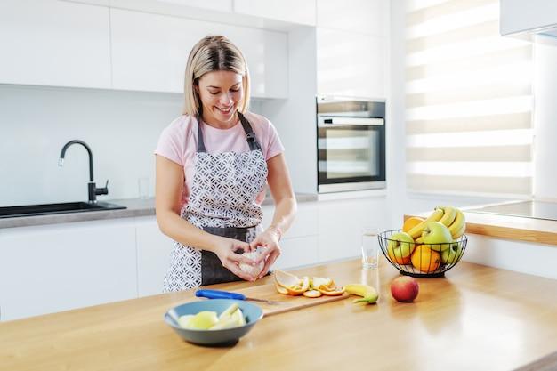 魅力的な笑顔の肯定的な白人金髪主婦のエプロンキッチンに立って、オレンジを剥離します。キッチンカウンターには果物があります。