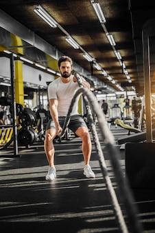 モダンなジムでバトルロープ運動を行う筋肉の健康的なハンサムな男。