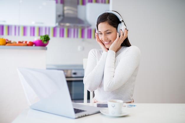 ゴージャスな陽気な少女は、コーヒーを飲みながらキッチンのテーブルに座っている笑顔のラップトップを見ながら彼女のヘッドフォンを保持しています。