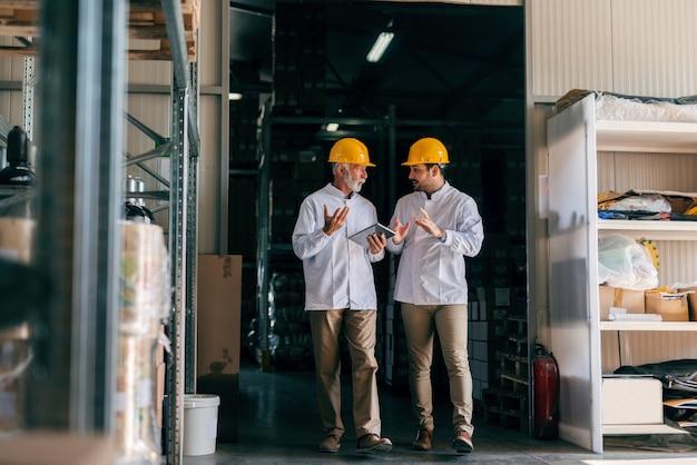 話し合い、歩く二人の男。収納インテリア。タブレットを手で保持しているシニア。