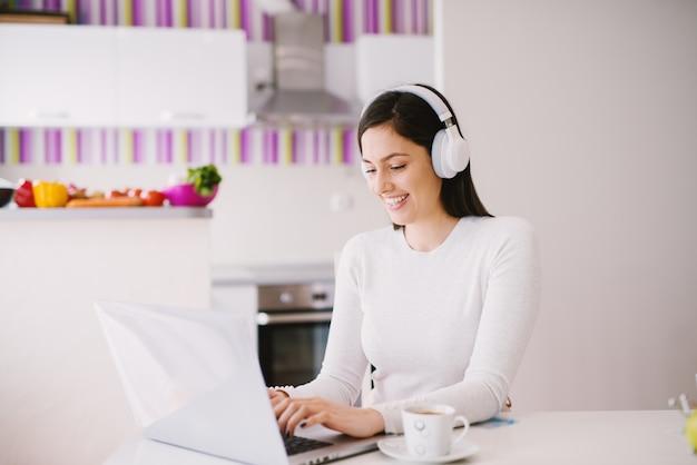 Симпатичная красивая молодая женщина использует свой ноутбук во время прослушивания музыки на гарнитуру и пить кофе в светлой комнате.