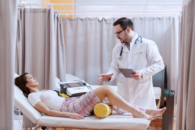 タブレットを押しながら患者の回復プロセスを説明する白い制服を着た若い白人医師。足の怪我をしていてベッドに横になった患者。病院のインテリア。