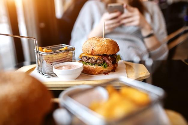 Фото вкусного гамбургера, картофеля фри и соуса на тарелке. в фоновом режиме женщина с помощью смартфона.