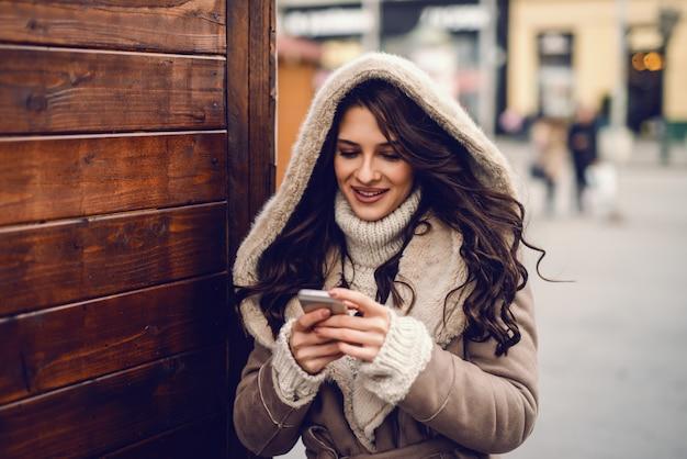 寒い気候で屋外に立っている間メッセージを読み書きするためのスマートフォンを使用してコートに身を包んだ豪華な白人女性のクローズアップ。