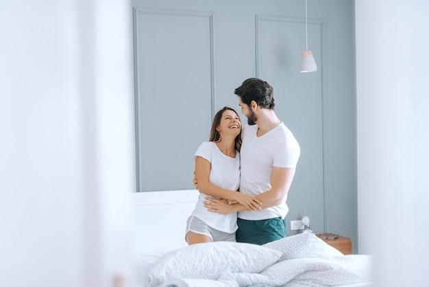 Счастливая пара кавказских в пижаме, улыбаясь и обнимая в постели по утрам. интерьер спальни.
