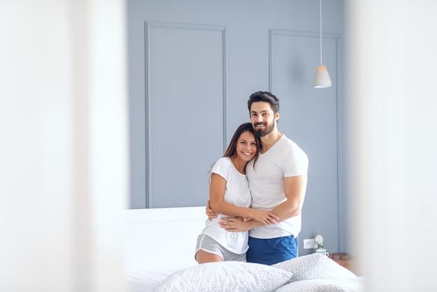 Счастливая пара кавказских в пижаме улыбается, обнимается в постели и смотрит в камеру. утреннее время. интерьер спальни.