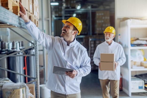注文とタブレットを保持している笑顔の白人倉庫の従業員。