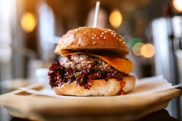 プレートにおいしいハンバーガーのクローズアップ。不健康な食事のコンセプトです。