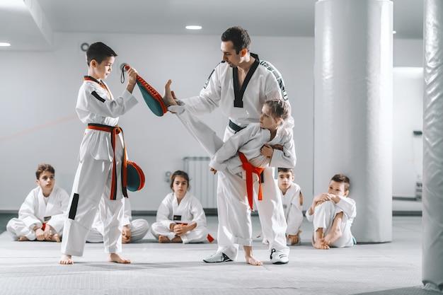 キックターゲットを蹴る方法を若い女の子に示すトレーナー。ターゲットを持つ男の子。テコンドートレーニングコンセプト。