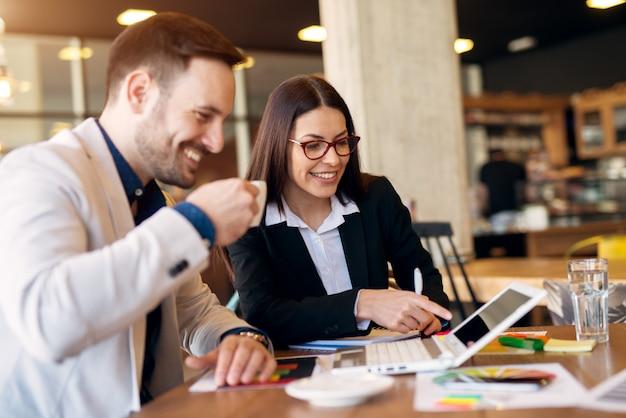 コーヒーショップに座っている間にいくつかの新しいアイデアを探している創造的な現代の若いビジネスカレッジ。ノートパソコンを見て、チャット。