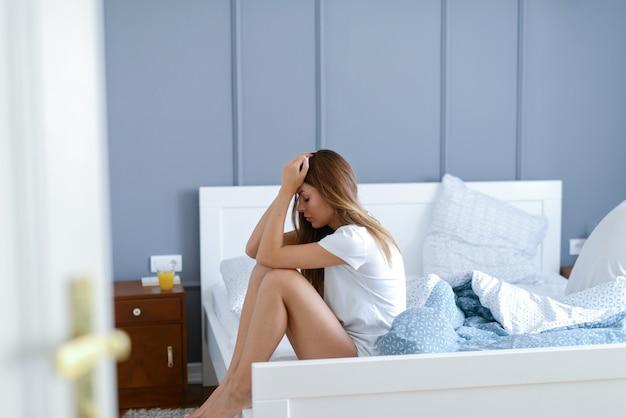 Красивая молодая девушка, сидящая на своей кровати с руками на ней. думая о своих проблемах, грустно.
