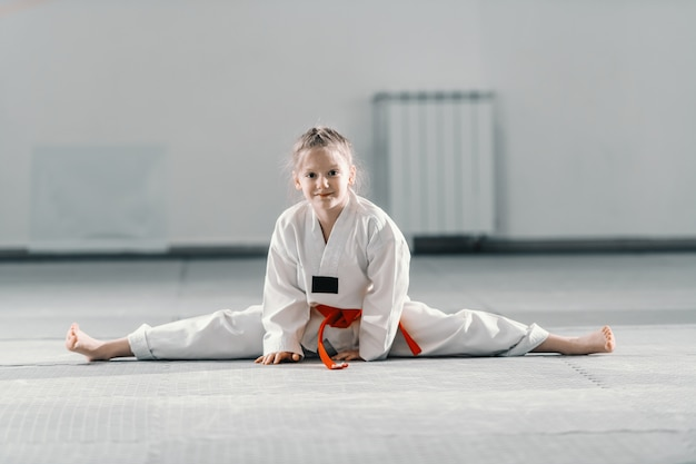 足を広げて床に座って、笑顔でカメラ目線のドボックの白人少女。テコンドートレーニングコンセプト。