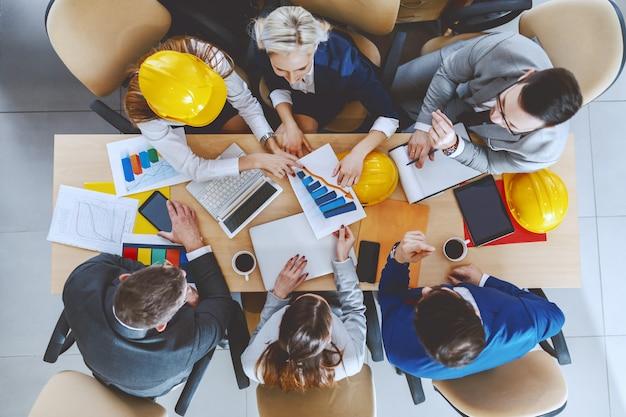 大きなプロジェクトに取り組んでいるフォーマルウェアの熱心な建築家のグループの平面図。机の上には、ラップトップ、タブレット、書類、チャート、コーヒーがあります。