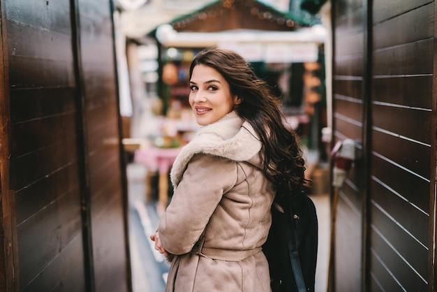 Красивая молодая девушка в зимнем пальто, стоя в уличном проходе. смотрю в камеру. красивая улица, украшенная рождеством.