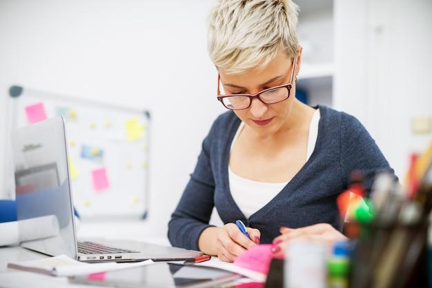 書類とノートパソコンをオフィスの机で働く焦点を当てた美しい中年ビジネス女性のクローズアップ。