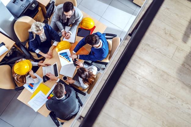 Вид сверху на шесть трудолюбивых архитекторов, сидящих в зале заседаний и встречающихся по поводу нового проекта.