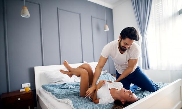 Игривый счастливый мужчина обнимает свою девушку и смеется, лежа на кровати.