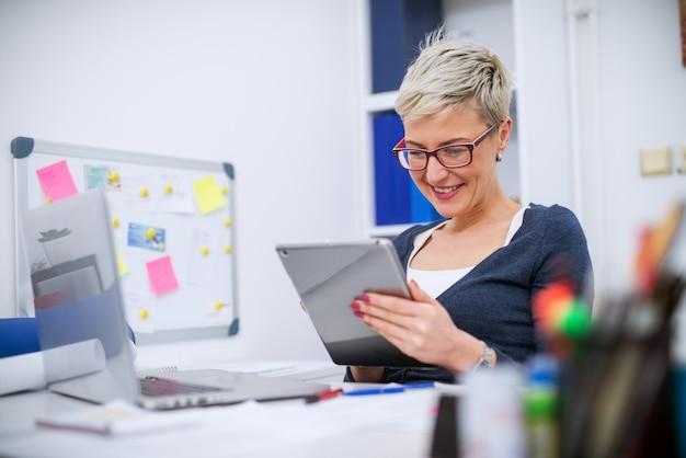 Крупным планом очаровательная довольная профессиональная женщина-менеджер с короткими волосами, сидящая в офисе и смотрящая в планшете.