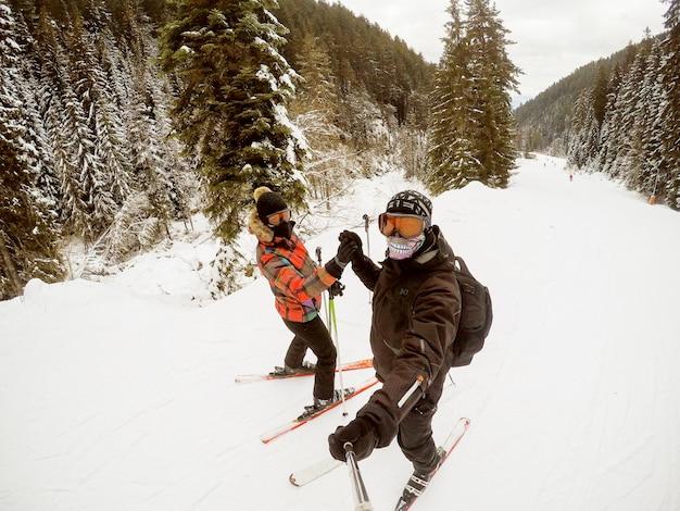 若い女性と男が休暇中に晴れた日にスキーをしながら手を繋いでいます。