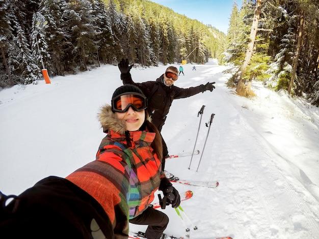 晴れた日に山でスキーを楽しむ美しい若いカップルは雪で覆われています。