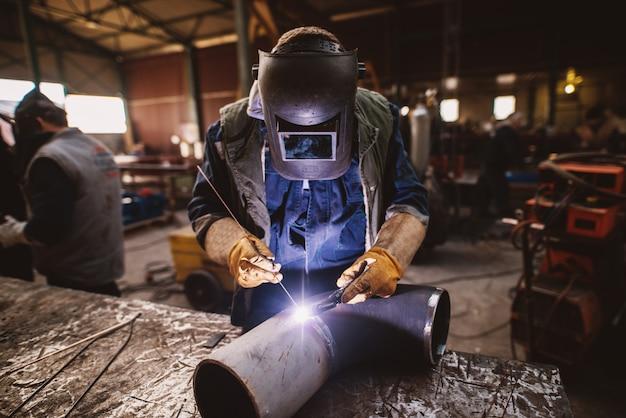 火花が飛んでいる間、防護服の溶接機と産業用テーブルのマスク溶接金属パイプ。