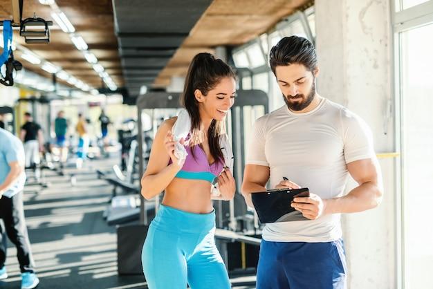 Подходит улыбается кавказская женщина с полотенцем вокруг шеи, глядя на буфер обмена. ее личный тренер пишет и показывает результат тренировок. интерьер спортзала.
