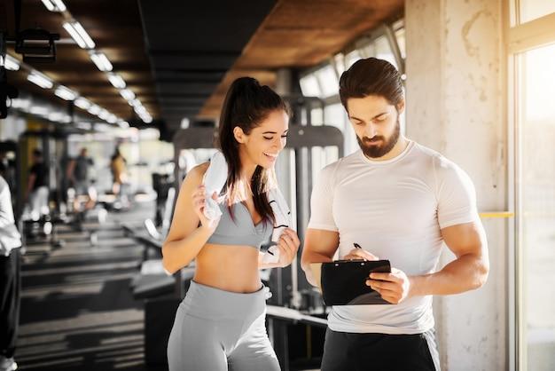 Молодая стройная фитнес-девушка, стоящая с полотенцем возле красивого тренера, показывая свое расписание на следующую неделю в тренажерном зале.