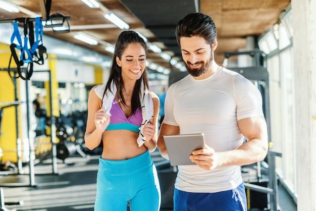 ひげを生やした笑顔のパーソナルトレーナーがタブレットでトレーニングの女性の結果を示します。彼の隣に立ってタブレットを見て女性。ジムのインテリア。