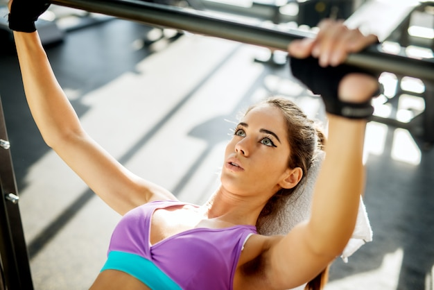 ジムのベンチでバーベルで運動をしている魅力的なかわいい若いスリムフィットネス女の子のクローズアップ。