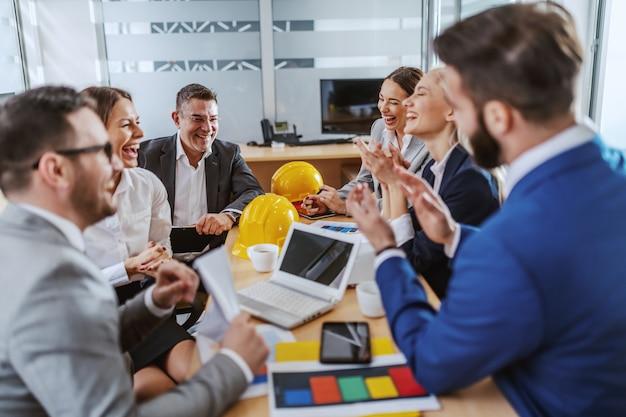 Группа веселых деловых людей сидит в зале заседаний, хлопает в ладоши и радуется успеху в новом проекте.