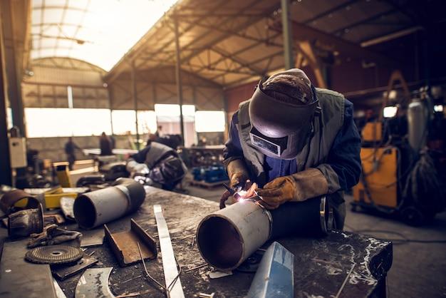 他の数人の労働者の前で工業用ファブリックのワークショップで金属彫刻に取り組んでいるプロのマスク保護溶接工男の縦向きビューを閉じます。