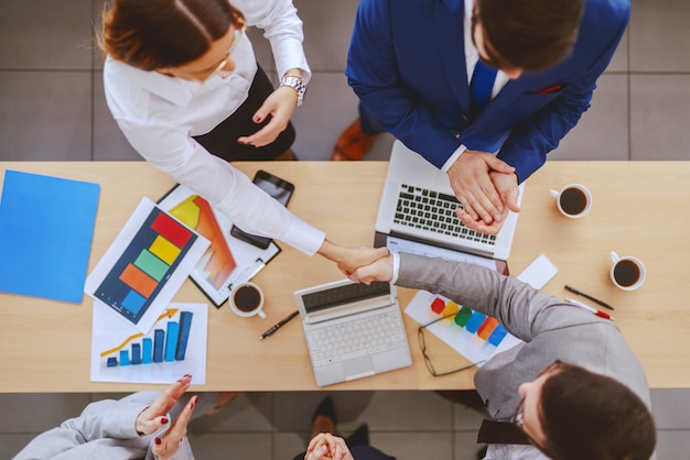 他の同僚が拍手しながら握手するパートナーの平面図。デスクの書類、コーヒー、ラップトップ。重要なのは見るものではなく、見るものです。