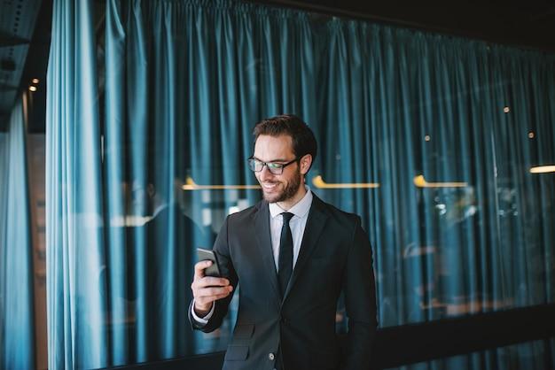 魅力的なエレガントな白人実業家のスーツとウィンドウの横に立っている間スマートフォンでメッセージを読む眼鏡。本社のインテリア。