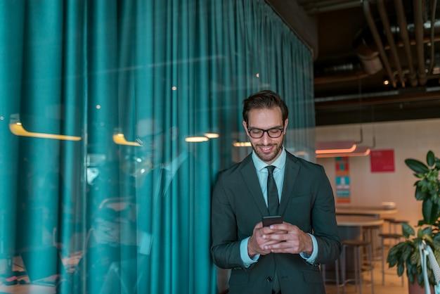 会議室の前に立って、スマートフォンを使用して笑顔の実業家。