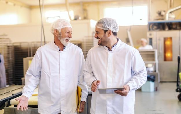 若い監督者が従業員に話して、笑って、トラフ食品工場を歩きながらタブレットを保持しています。