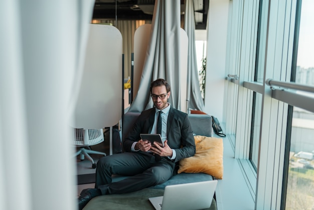 Счастливый бизнесмен расслабляющий в своем офисе и с помощью планшета. рядом с ним окно.