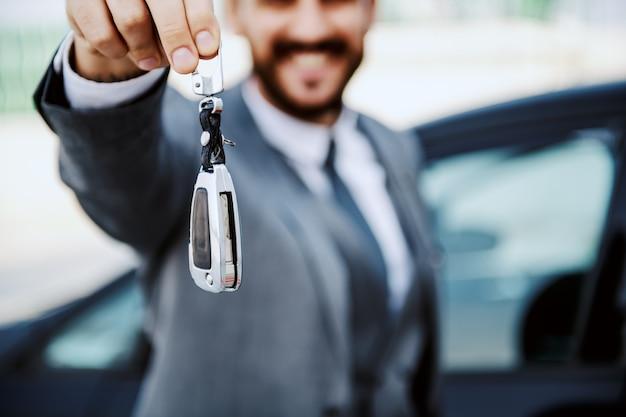 Закройте бородатого бизнесмена, показывая ключи от машины. селективный акцент на клавишах.