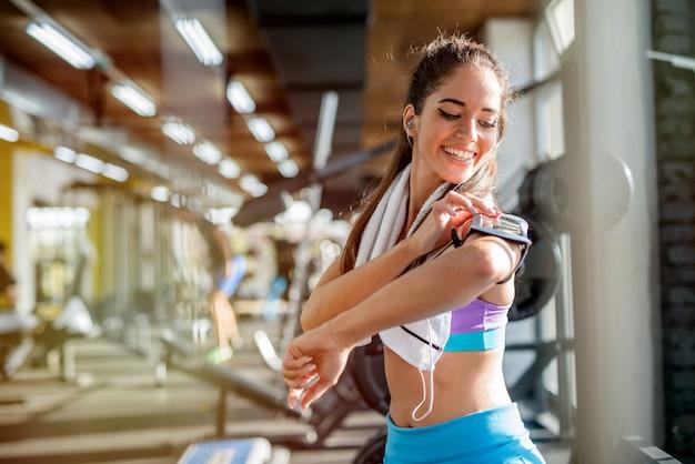 トレーニングのための彼女の自己を準備するジムでかわいい笑顔のスポーティな女の子の写真。彼女の電話で音楽を選ぶ。