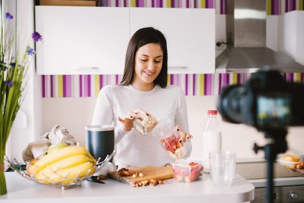 美しい少女は、カメラの前ですでに新鮮な果物で満たされたミキサーボウルに穀物を入れています。