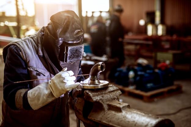 機械の新しい部分に取り組んでいる保護服の男性労働者のクローズアップ。