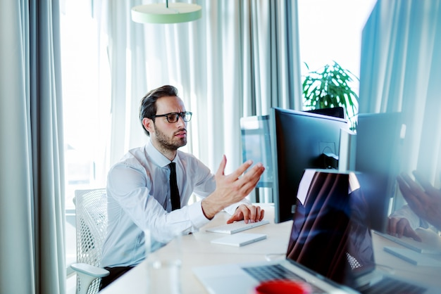 腹を立てている企業のビジネスマンは、オフィスに座っているときにデスクトップコンピューターでエレガントな作業をしました。