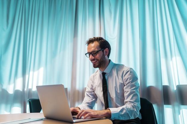 オフィスに座っている間ラップトップを使用して笑顔の実業家。キーボードの手。背景のカーテンに。