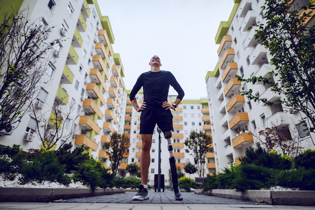 建物に囲まれた屋外の腰に手で立っている義足でハンサムなスポーツマンの低角度のビュー。