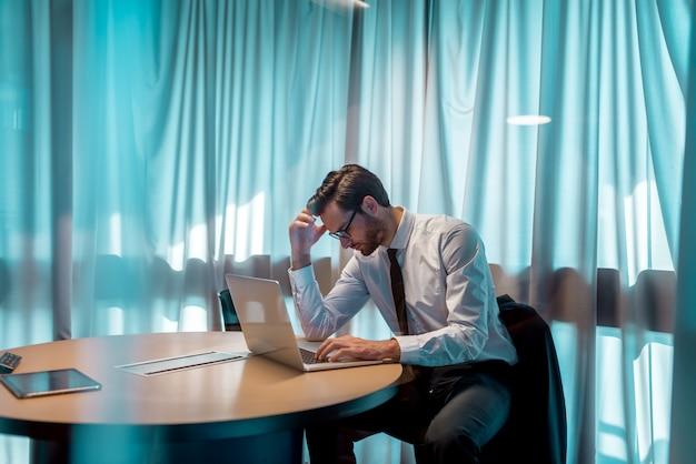 オフィスに座っている間ラップトップを使用して心配している実業家。キーボードに手。背景のカーテンに。